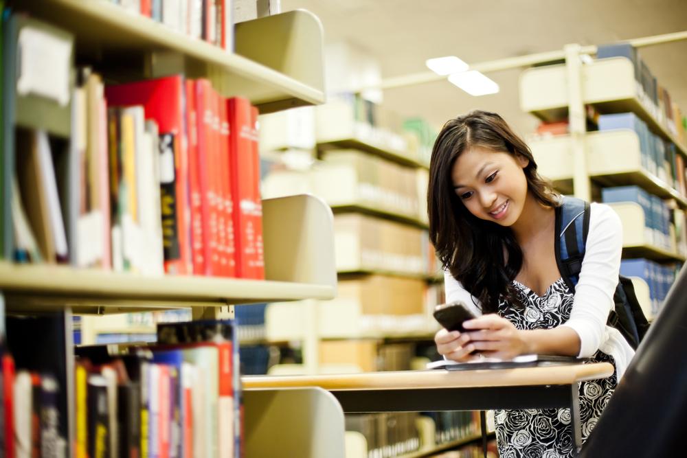 図書館でスマートフォンを見る女性