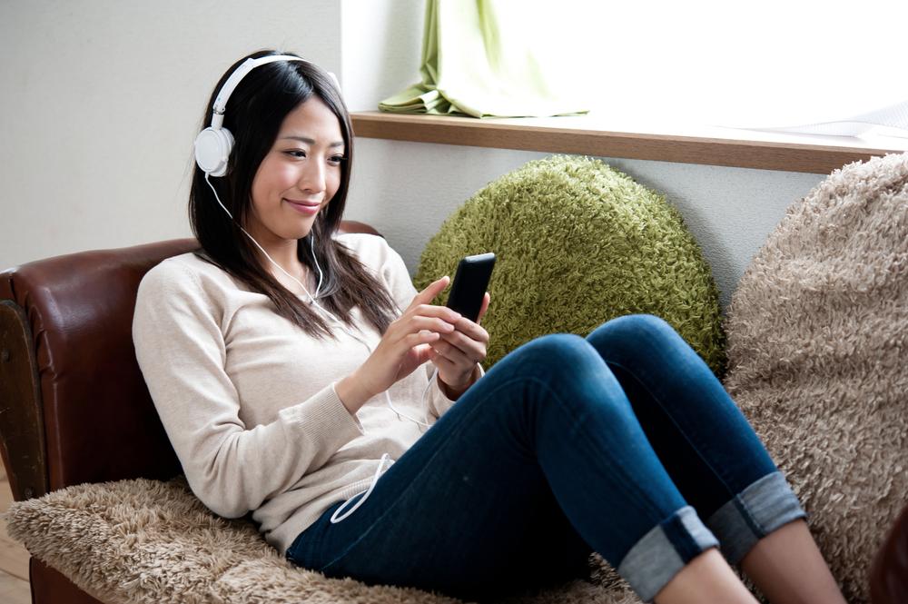 ヘッドホンをしてスマートフォンを楽しむ女性