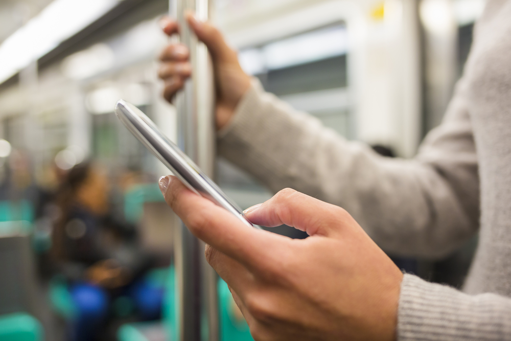 地下鉄でスマートフォンを楽しむ人